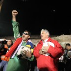 Chilean president Sebastian Pi–era sings the national anthem with chief supervisor Luis Urzua, the last miner out of the rescue hole at the San Jose mine near Copiapo, Chile on October 13, 2010. HUGO INFANTE/GOVERNMENT OF CHILE