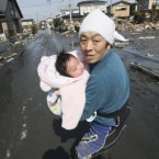 This man had just been reunited with his four-month-old baby girl who was miraculously found alive in the rubble of tsunami-torn Ishinomaki on Monday. (AP Photo/The Yomiuri Shimbun, Hiroto Sekiguchi)