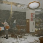 People react at a book store in Sendai as the ceiling begins to collapse. (PA Images)