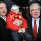 Enda Kenny and Eamon Gilmore with Darragh O'Neill, 4, as they announced they were going to form a coalition government. (PA Images/Niall Carson).
