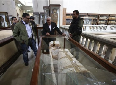 Zahi Hawass standing near the broken vitrine containing the damaged New Kingdom coffin.