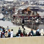People evacuated to a rooftop of a building look at other buildings damaged by tsunami tidal waves at a port in Kesennuma in Miyagi Prefecture. (AP Photo/Keichi Nakane, The Yomiuri Shimbun)