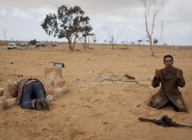 A Libyan rebel prays next to his gun while another kneels over the grave of his brother who was killed in fighting on the outskirts of Adjabiya, south of Benghazi.