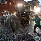 One reveller doesn't want to go home as city trucks clean up the French Quarter of New Orleans after Mardi Gras. (AP Photo/Patrick Semansky)