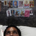 Religious images cover a wall above a student who holds a hunger strike outside the UN offices in Caracas, Venezuela, to demand the government an increase in the university budgets. (AP Photo/Fernando Llano)