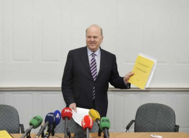 Minister Michael Noonan, bearing a copy of the Nyberg Report yesterday.
