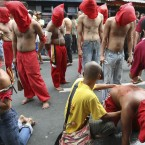 Hooded penitants flagellate themselves in front of a Catholic chapel in the Philippines<span class=