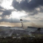 A helicopter drops water on a gorse fire outside Pontoon