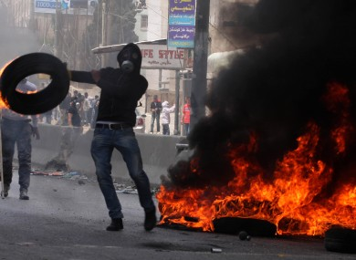 Palestinians clash with Israeli soldiers at an Israeli checkpoint between Jerusalem and Ramallah