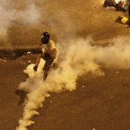 A helmeteA helmeted demonstrator tries to kick back a tear gas canister during a demo in Athens. Pic: APd demonstrator tries to kick back a tear gas canister during a demo in Athens