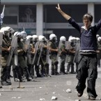 A protester raises his hands against riot police during a demonstration in Athens. Pic: AP Photo/Petros Giannakouris