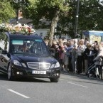 Members of the public applaud on Main Street in Blanchardstown Village, as the hearse carrying the coffin of former Minister for Finance Brian Lenihan TD leaves Jennings Funeral Home for St Mochtas Church in Porterstown. <span class=