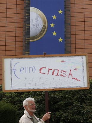 A man holds a sign outside the EU HQ in Brussels, where the two-day summit will take place