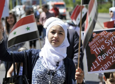 A young woman joins a solidarity protest for Syria in Switzerland.