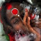A Hindu holy woman smokes cannabis during the Karchi Festival near Agartala, India (AP Photo/Sushanta Das)