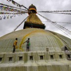 A worker throws a bucket of orange paint as the Boudhanath Stupa in Katmandu, Nepal, is cleaned. (AP Photo/ Niranjan Shrestha)
