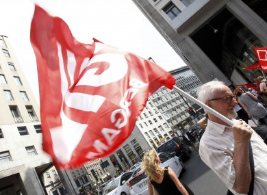 An aged Italian CGIL trade unionist holds a flag during a demonstration against the government in downtown Milan this week