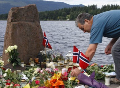 A man places a Norwegian flag between flowers in Utvika in front of Utoya island