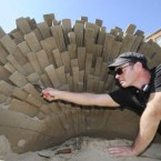 Sand sculptor Fergus Mulvaney works on his piece representing 'West'