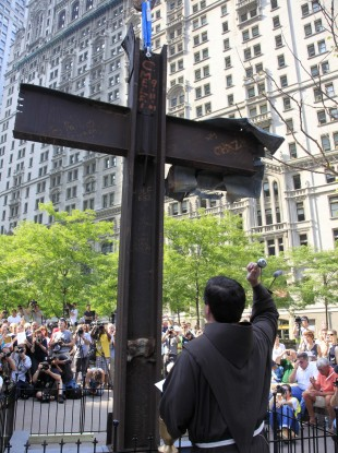 Rev. Brian Jordan sprinkles water on the Ground Zero cross during a ceremony in July. American Atheists has filed a lawsuit asking for its removal.