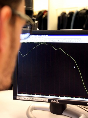 A worker looks at graph showing the FTSE 100 index from mid July to August 5th