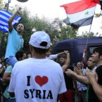 Syrians who live in Greece and Greek supporters shout slogans outside the Syrian embassy in Athens as Syrian troops killed nearly 100 people in two days. (AP Photo/Thanassis Stavrakis)