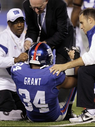 New York Giants defensive back Deon Grant is helped up by trainers during the first quarter against the St. Louis Rams on Monday.