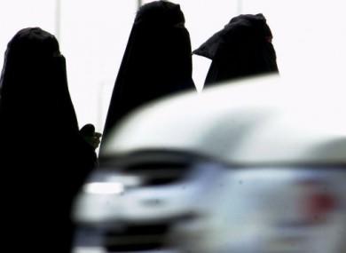 Saudi women walk past a car in Riyadh