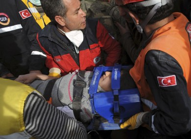 Workers carry a rescued youth from a building in Ercis