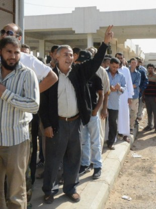 People stand in line to see the body of former Libyan leader Muammar Gaddafi outside a refrigeration room where his body is being kept in the suburbs of Misrata.