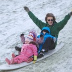 Tony Brennan with Lucy (5), Brian (3) and Erin (2) from Ballyfermot, slide down a hill on a surf board in the in the Phoenix Park.