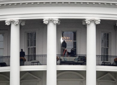 Law enforcement officers photograph a window at the White House in Washington.  A bullet hit an exterior window of the White House and was stopped by ballistic glass, the Secret Service said.