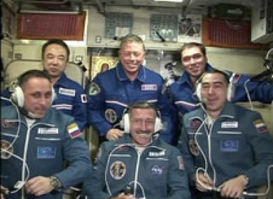 The new arrivals sit in front after being welcomed aboard the ISS.