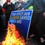 27 November 2010: Protesters burn a poster of Brian Cowen from his Lisbon Treaty Campaign.They are pictured outside the Dail protesting over the Government asking the International Monetary Fund and Europe for a multibillion bailout and the four year plan of cuts. (Photocall Ireland)