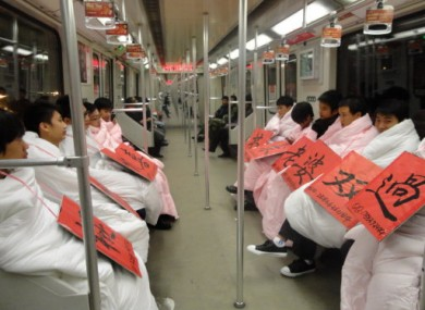 Young men wrapped in quilts are wearing signboards with their contact information to show their desire for a wife ahead of next week's Singles Day. 11/11/11 is a Chinese pop culture holiday for people who are still living the single life.