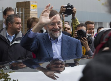 Conservative Popular Party candidate Mariano Rajoy waves after voting at a polling station in Madrid