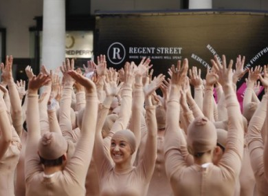 A giant human hand is formed by 200 in London's Covent Garden to visually illustrate Dupuytren's contracture, a progressive and debilitating hand condition.