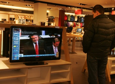 A man watches Brendan Howlin make his Budget announcement in a shop window today