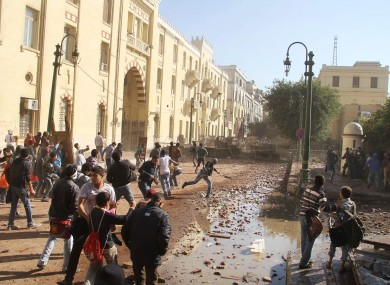 Protesters throw rocks toward Egyptian military in front of the former building of the American University of Cairo