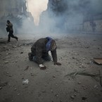 A protester overcome with tear gas kneels in the middle of the street during clashes with the Egyptian riot police on 20 November, 2011. Protesters demanded that the ruling military quickly announce a date to hand over power to an elected government. (AP Photo/Tara Todras-Whitehill/PA Images)