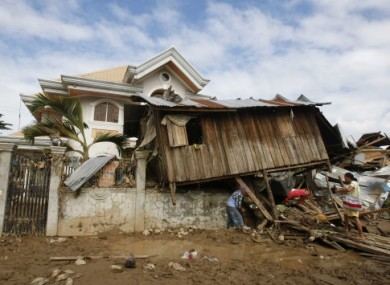 19 December: Locals retrieve items from their house which landed on a fence during Typhoon Washi in Iligan city, Philippines. .