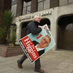 Socialist Party and United Left Alliance candidate Joe Higgins with his election poster outside the offices of then Anglo Irish Bank. Pic: Julien Behal/PA Wire.