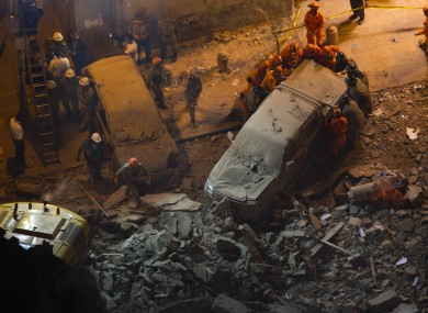 Rescue worker remove a car after a building collapsed in Rio last night