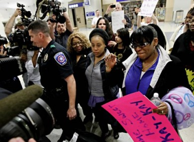 Jakadrien Lorese Turner, centre, is surrounded by family and friends as she leaves Dallas-Fort Worth International Airport yesterday.
