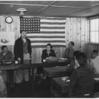 Roy Takeno addressing a 'Town Hall' meeting with an American flag on the wall behind him. (Library of Congress, Prints & Photographs Division)