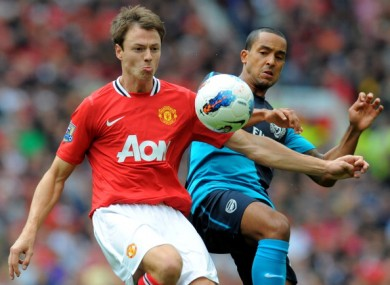Jonny Evans tussles with Theo Walcott.