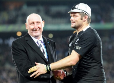 New Zealand All Black captain Richie McCaw is honored with his 100th cap as he shakes hands with former player Jock Hobbs last year.