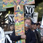 Actor Martin Sheen carries a cross as he marches in a procession around the Federal Building in Los Angeles during a prayer vigil for peace in 2003. (AP Photo/Nick Ut)<span class=