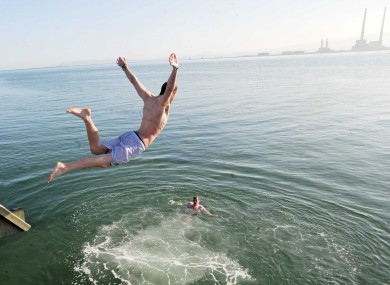 Jonny McKeown from Artane throws himself into the sea off Bull Island in Dublin yesterday