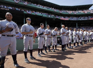 New York Yankees players stand for the national anthem in throw-back uniforms.